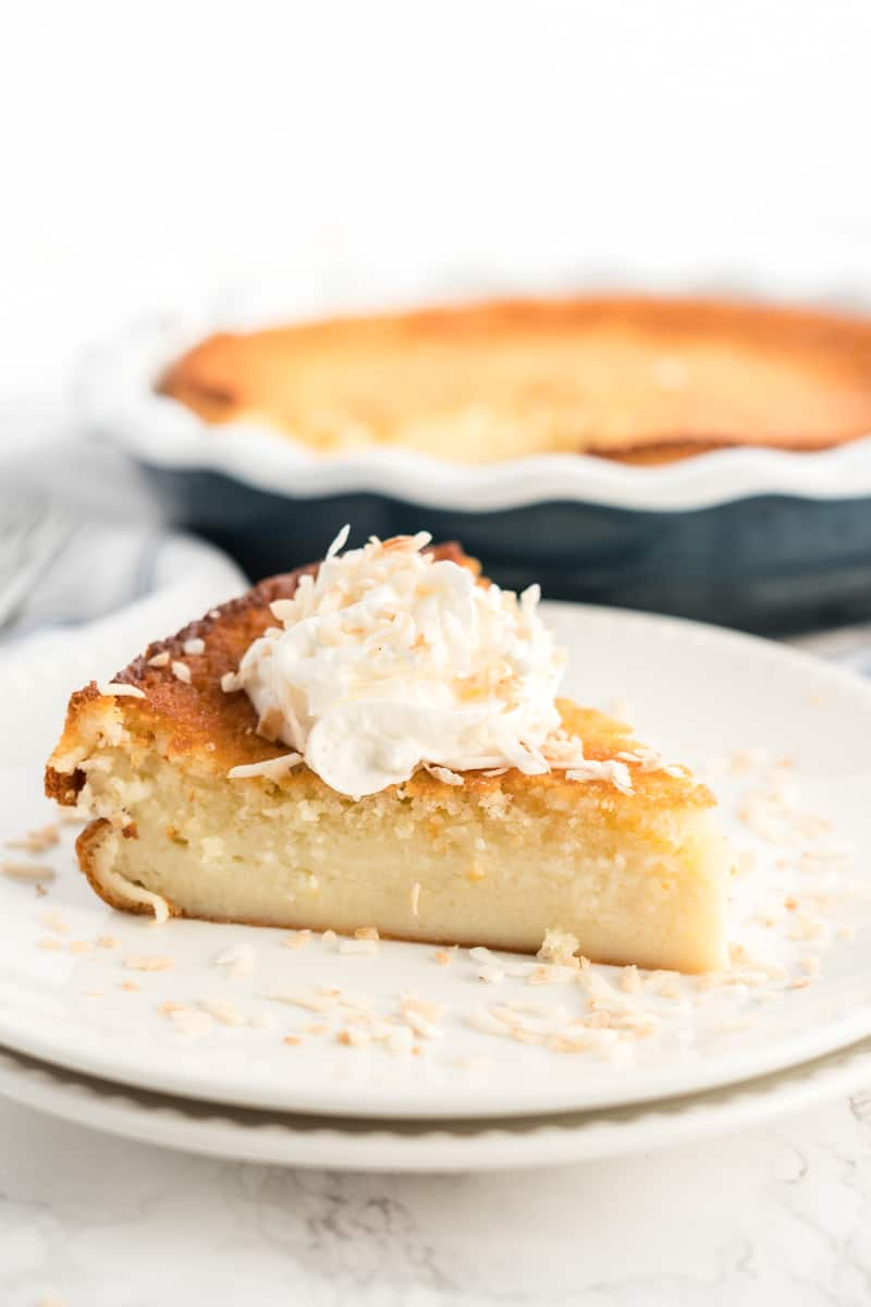 Slice of Impossible Pie on plate topped with whipped cream and toasted coconut