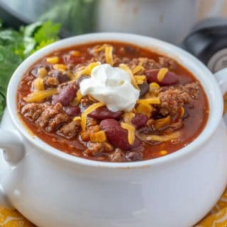 Chili in white bowl garnished with shredded cheese and sour cream