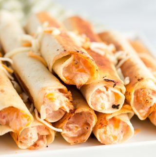 Taquitos on serving plate sprinkled with shredded cheese