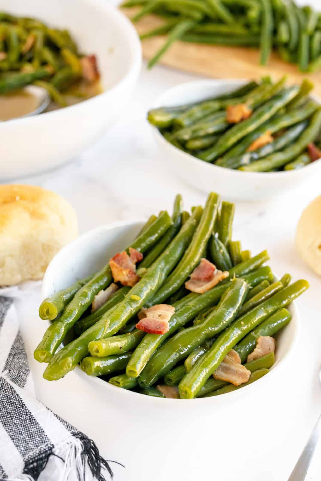 Close up of Southern Style Green Beans in white bowl showing bacon