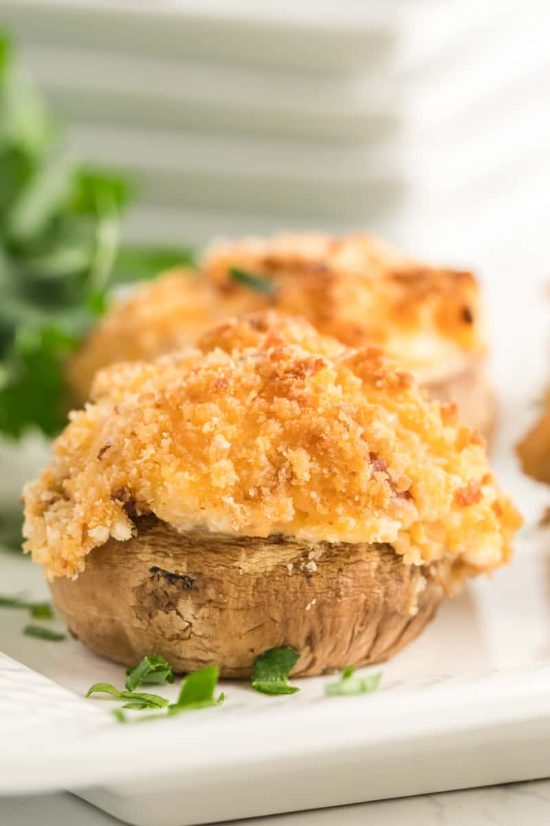 Close up of one mushroom on plate showing golden top and crispy breadcrumbs