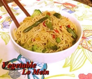 Lo mein i bowl topped with vegetables and chopsticks