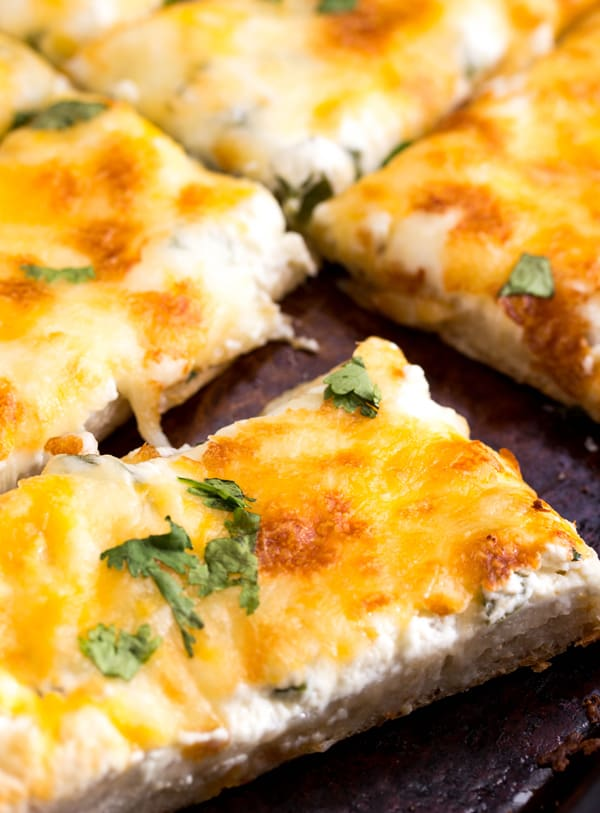 Jalapeno popper breadstick sliced showing slight cheese pull topped with cilantro