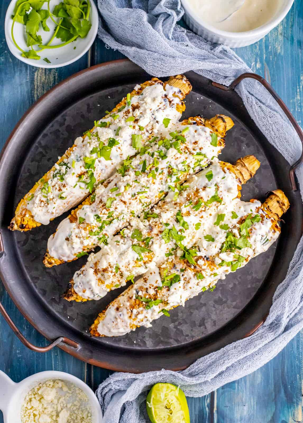 Finished Mexican Street Corn on platter lined up in a row with ingredients surrounding platter