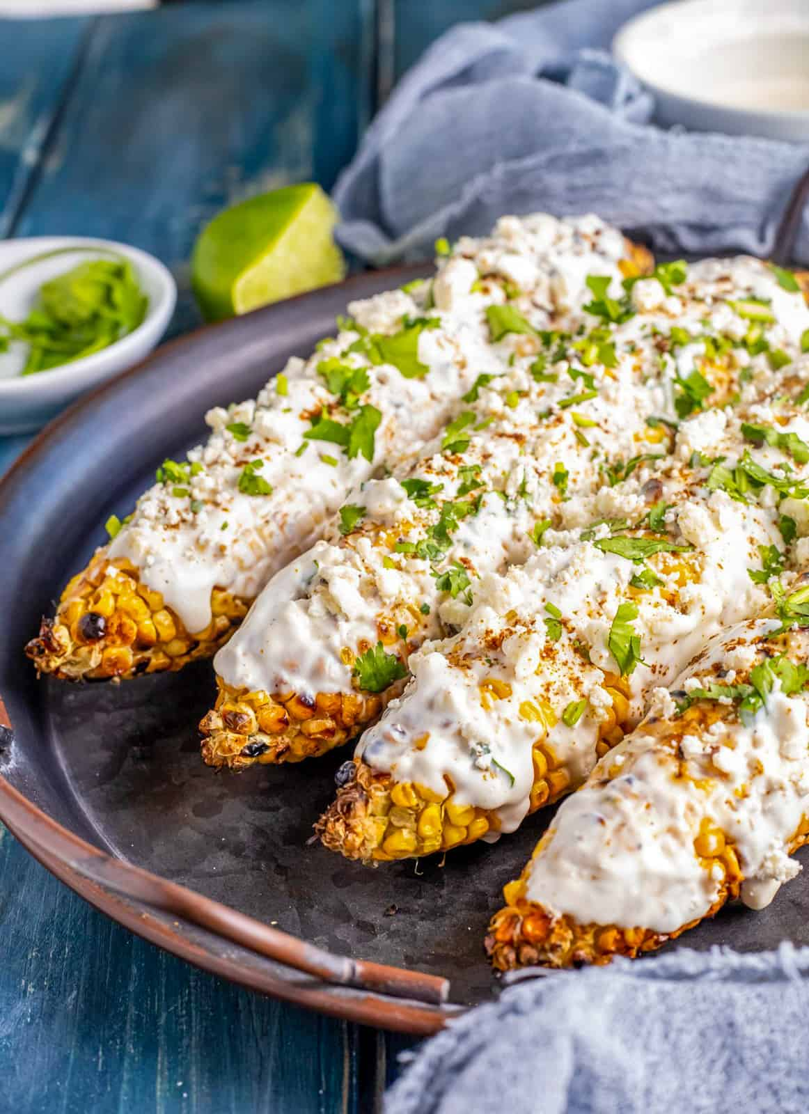 Finished Street Corn Recipe on platter with lime in background