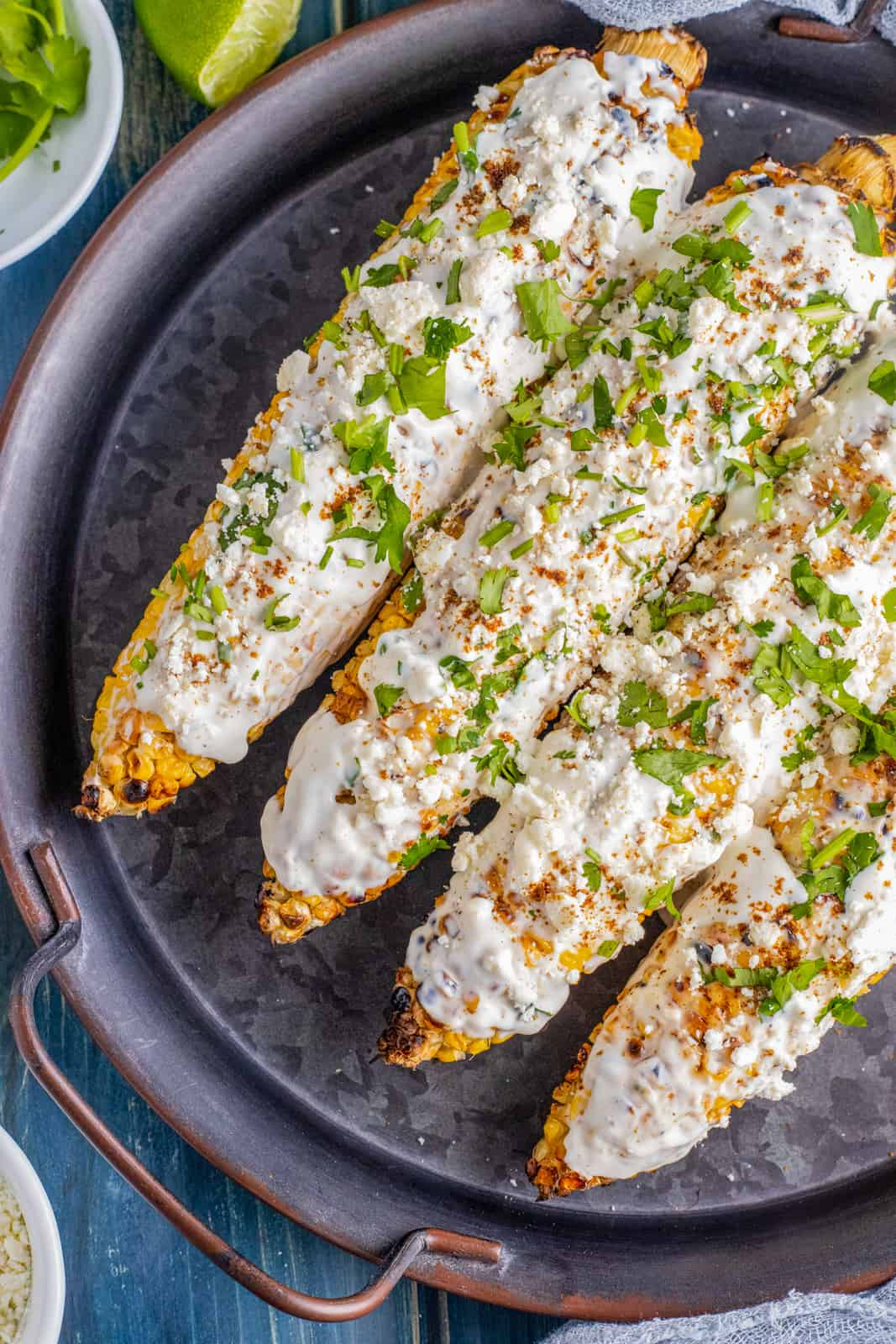 Overhead of finished corn on black platter topped with cilantro