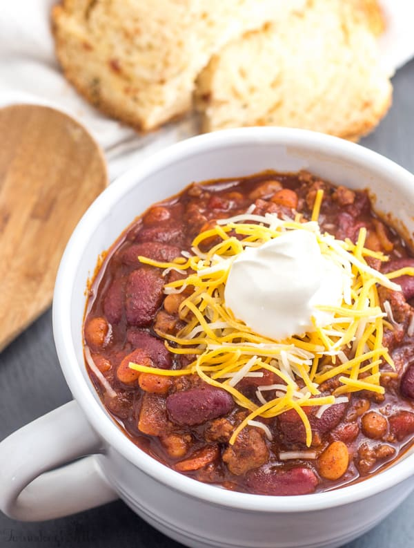 Finished Sweet Heat Chili in bowl garnished with cheese and sour cream