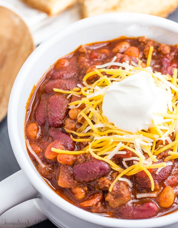 Overhead photo of chili in white handled bowl topped with shredded cheese and sour cream