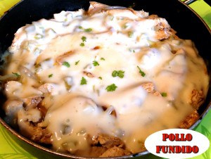 Pollo Fundido in large pan finished topped with melted cheese sauce and chopped cilantro