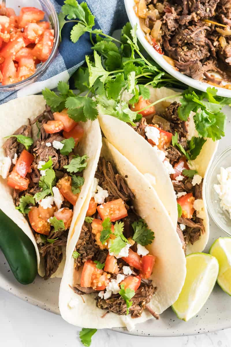 Barbacoa Beef served as tacos on plate topped with cheese, tomatoes and cilantro