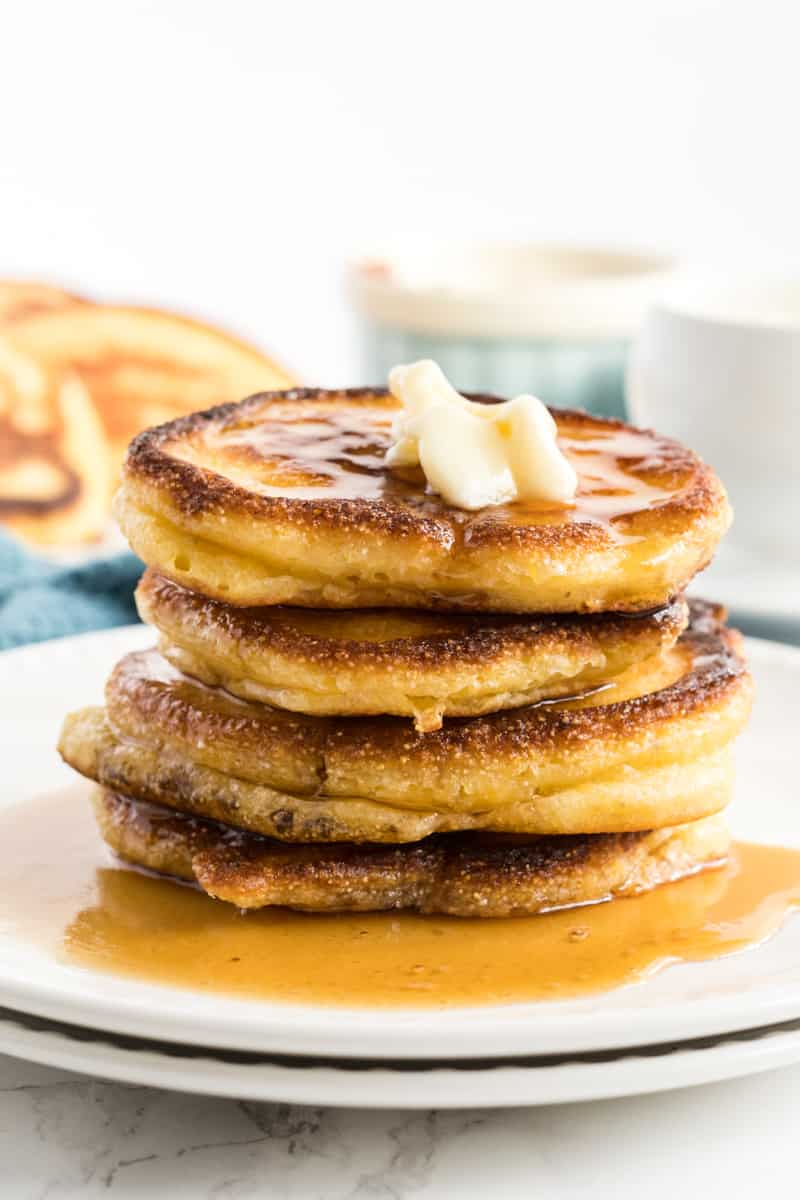 Hoe Cakes stacked on top of one another with butter and drizzled with syrup