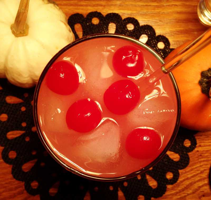 Overhead photo of floating cherries and ice in glass with pumpkins decorating it