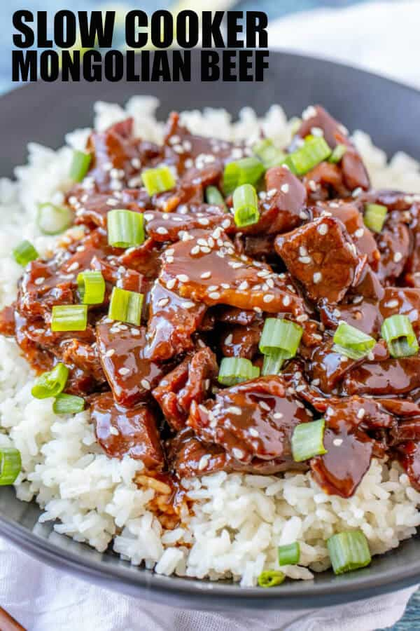 Pinterest image of Mongolian beef on black plate over rice topped with green onions and sesame seeds