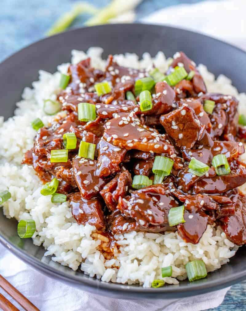 Mongolian Beef over rice topped with sliced green onions and sesame seeds