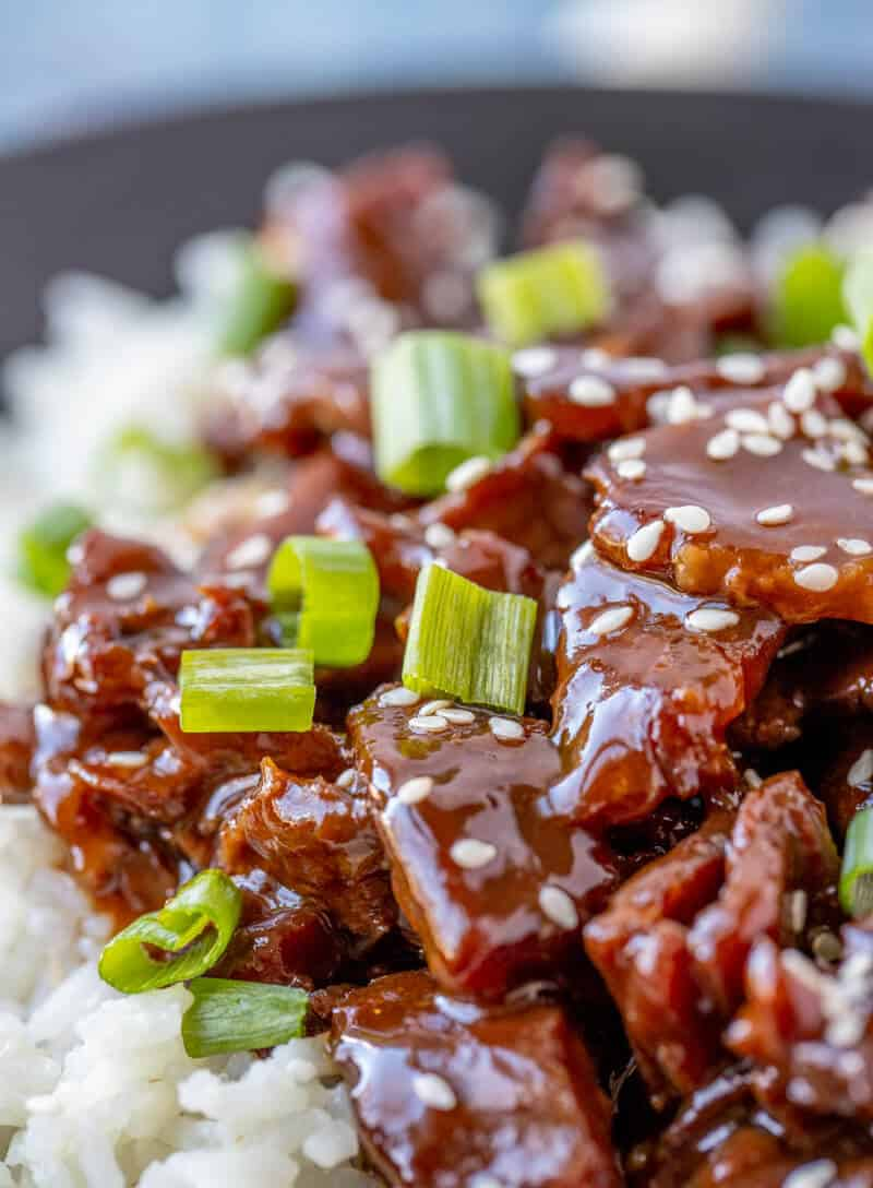 Close up of glazed Mongolian beef with green onions and sesame seeds