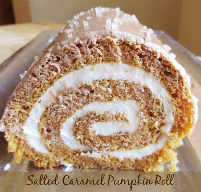 Close up photo of pumpkin roll on silver platter showing the cream filling and title on bottom