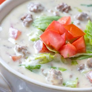 Cheeseburger soup in white bowl