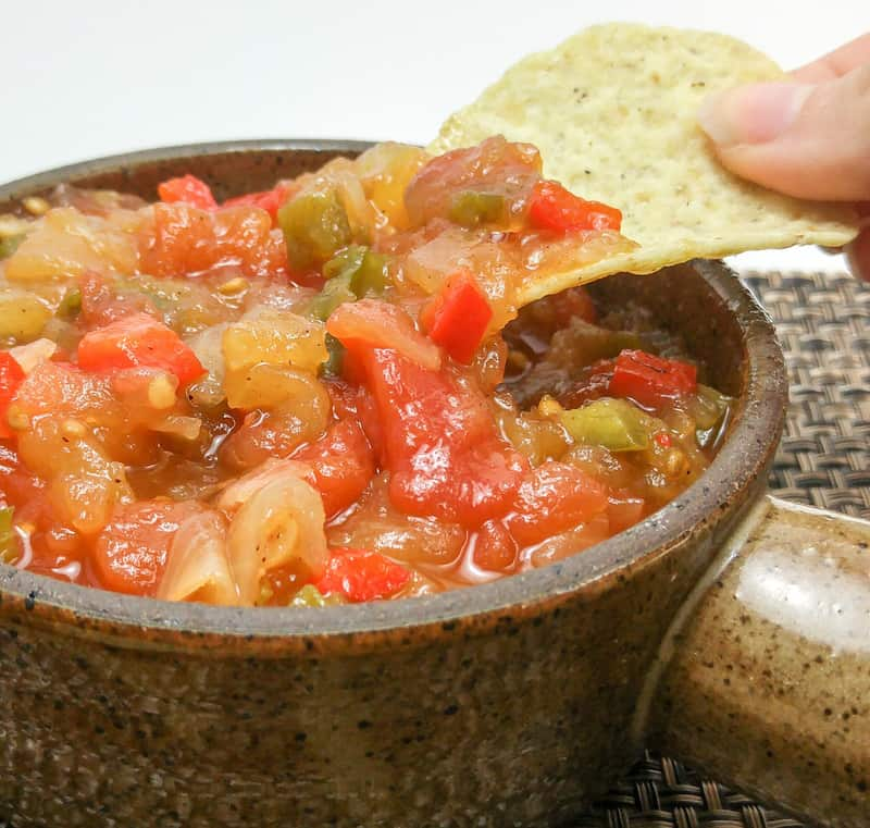 Hand dipping chip into salsa in brown serving dish