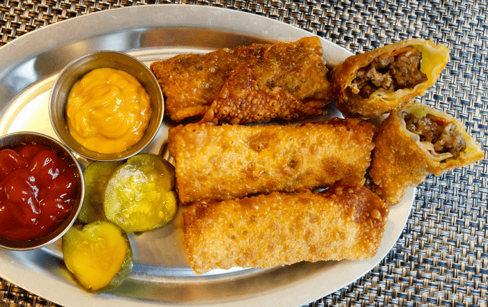 Overhead of crispy fried egg rolls served with mustard, ketchup and pickles