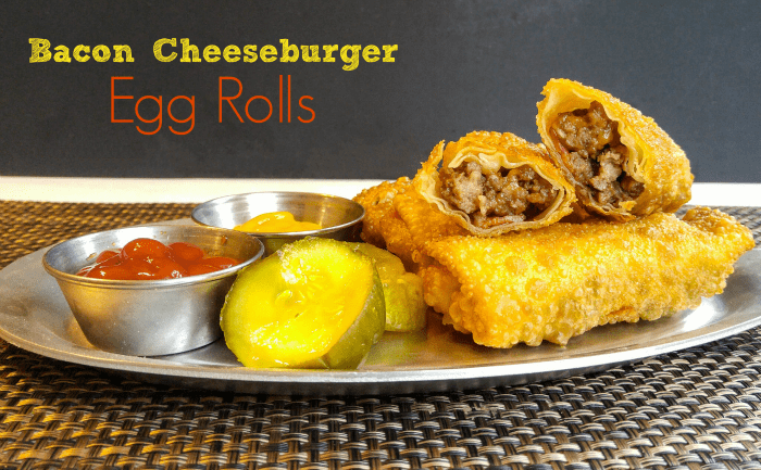 Egg Rolls on silver platter with one cut in half serve with pickles, mustard and ketchup