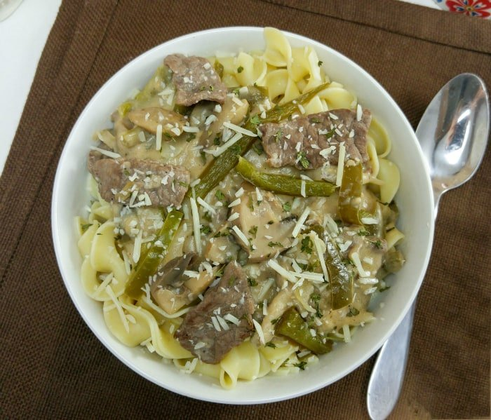 Overhead of stroganoff in white bowl showing beef and green peppers