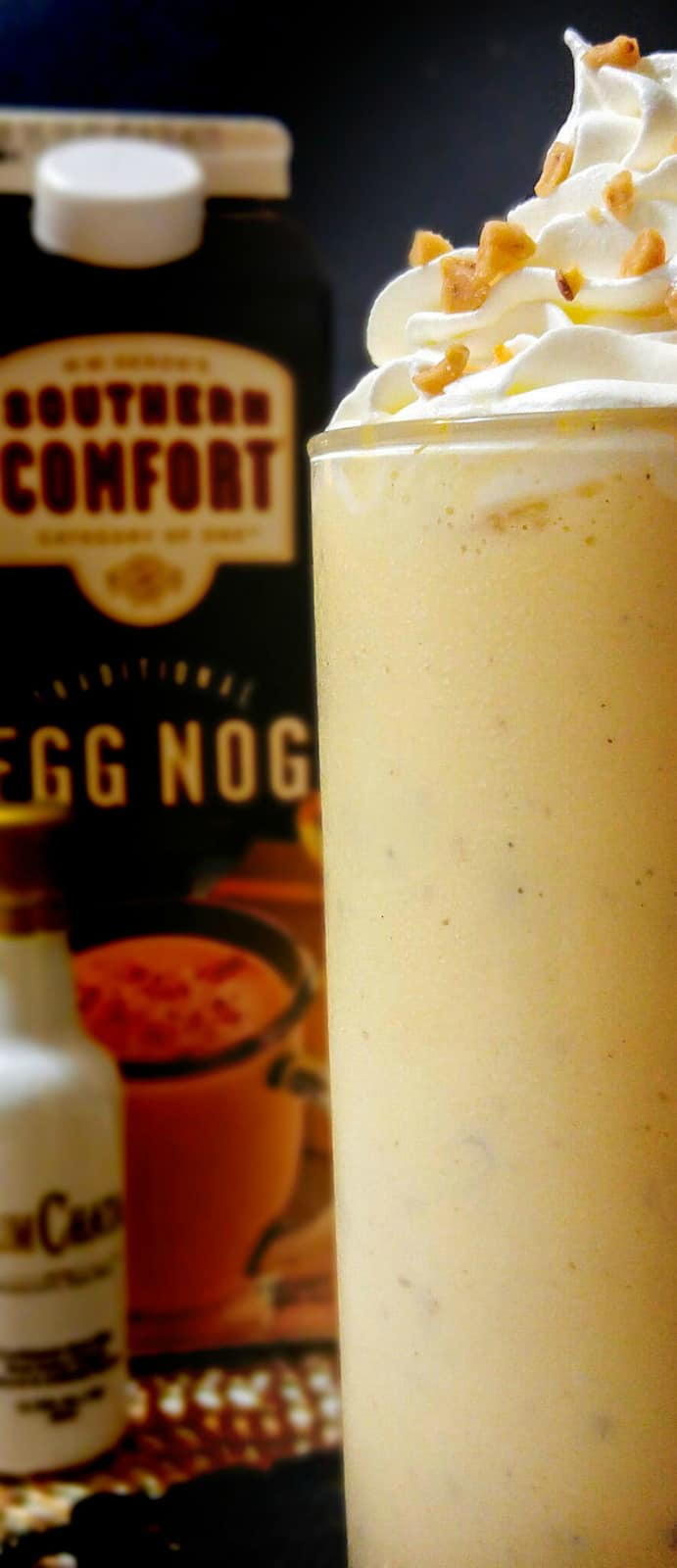 Boozy Egg Nog Shake with bottle of egg nog and rumchata in background