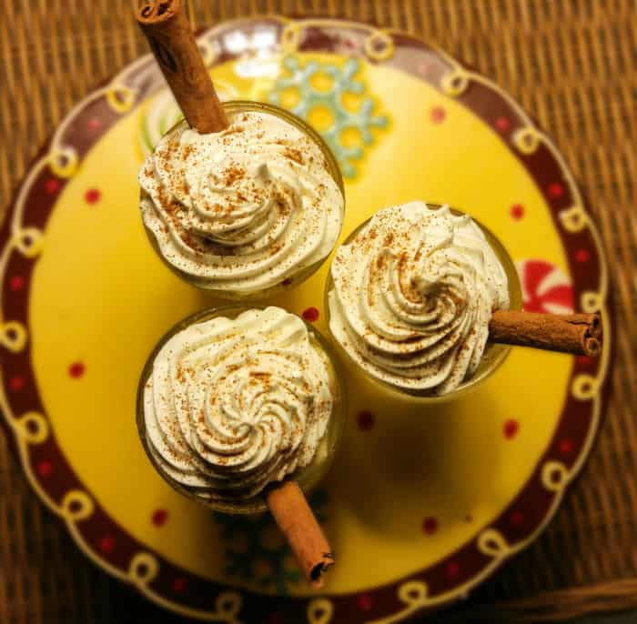 Overhead of jello shots on decorative platter showing whipped cream and cinnamon