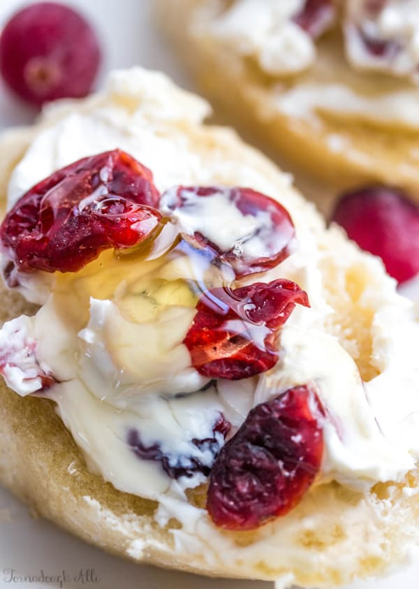 Close up of goat cheese on sliced baguette topped with dried cranberries and honey