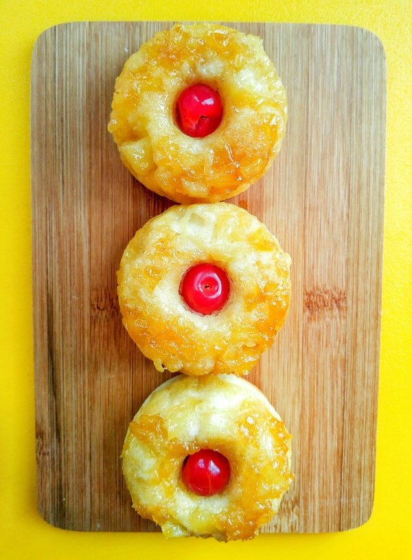 Overhead of three donuts with cherry in center on wooden board