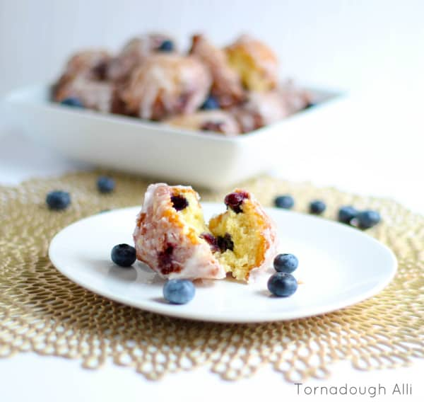 One split Fritter on white plate with blueberries