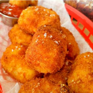 Cheesy Tater Tots in red bar basket topped with sea salt