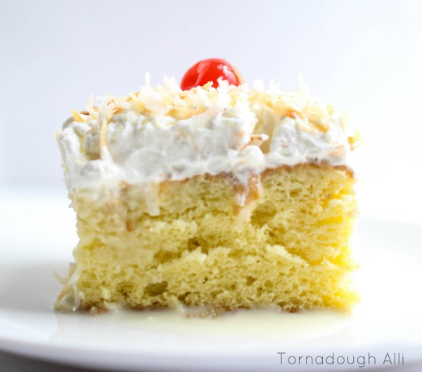 Tres Leche Cake side showing whipped topping coconut and cherry