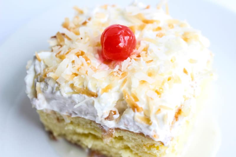 Slice of cake on plate with whipped topping, coconut and cherry