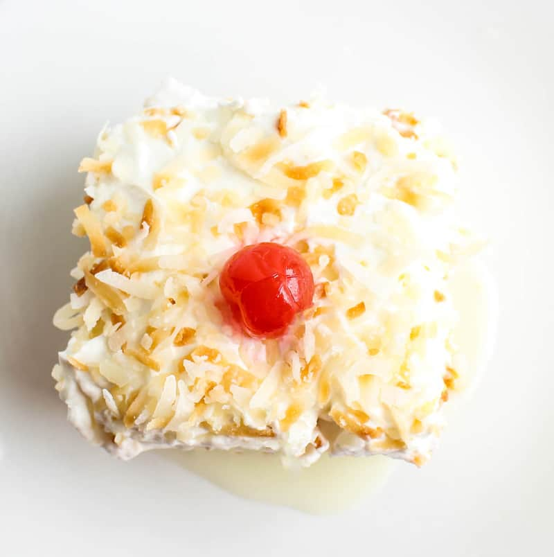 Overhead slice of cake on plate topped with toasted coconut and cherry