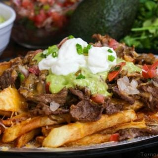 Carne Asada Fries dressed on silver tray