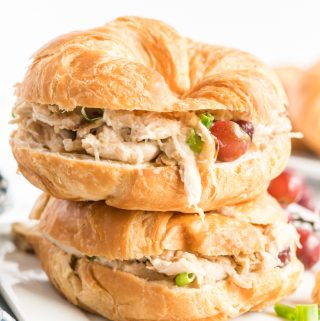 Two chicken salad sandwiches in croissants stacked not op of on another