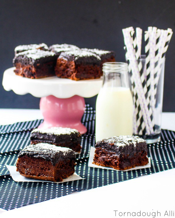 Oreo Truffle Brownies on parchment paper with cake stand of brownies in background