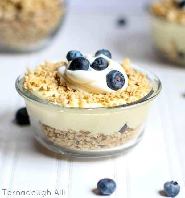 Layered granola lemon filling and more granola topped with whipped cream and blueberries