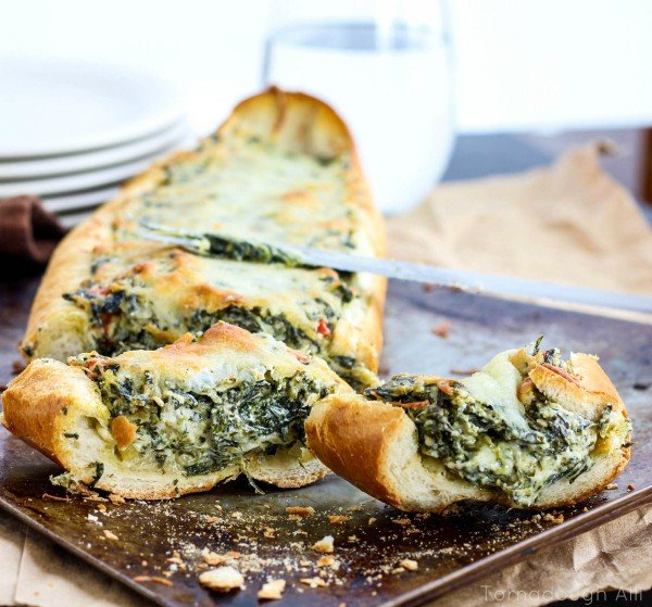 Spinach Dip Stuffed French Bread on pan with two slices cut