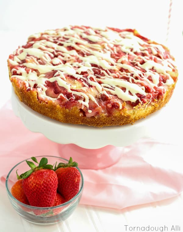 Upside Down Strawberries and-Cream Cake on pink and white cake stand with cream cheese glaze