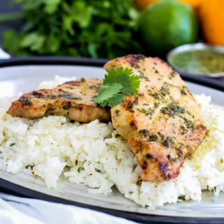 Mojo Pork Chops with Rice on platter over rice with cilantro