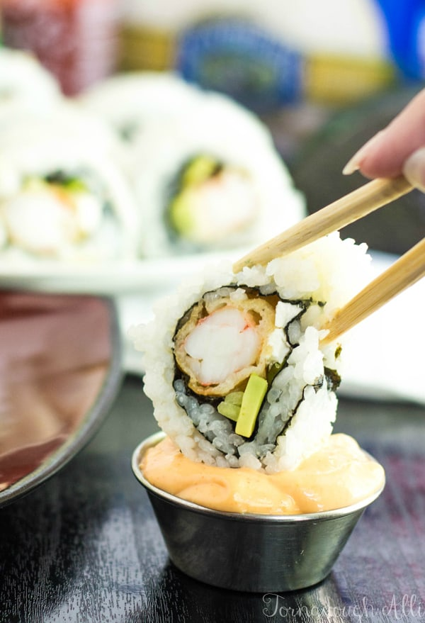 Chopsticks dipping sushi roll into sauce