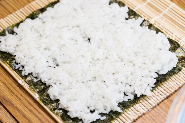 Rice on seaweed on sushi roller