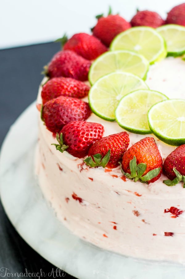 Strawberry Lime Cake on marble stand topped with strawberry and lime slices