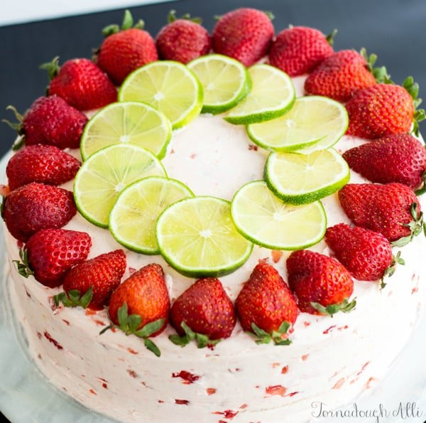 Overhead of finished cake topped with sliced strawberries and limes