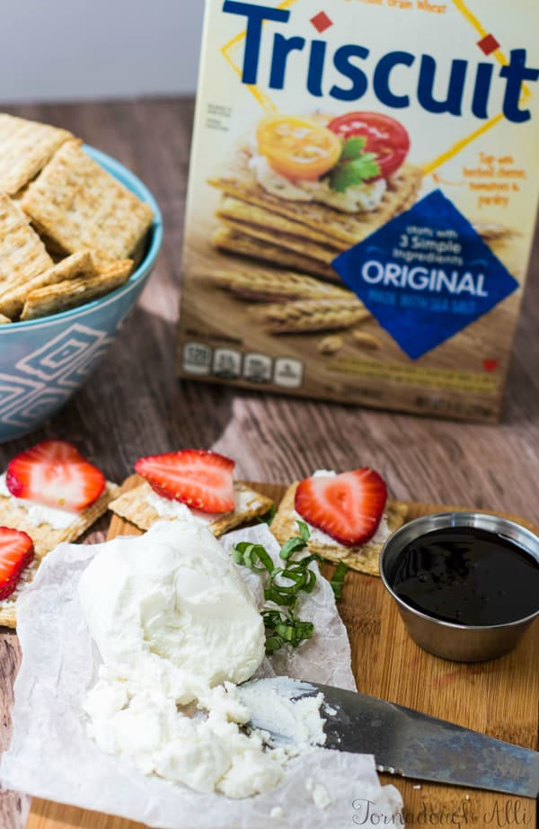 Cheese on board with strawberries, crackers and balsamic sauce