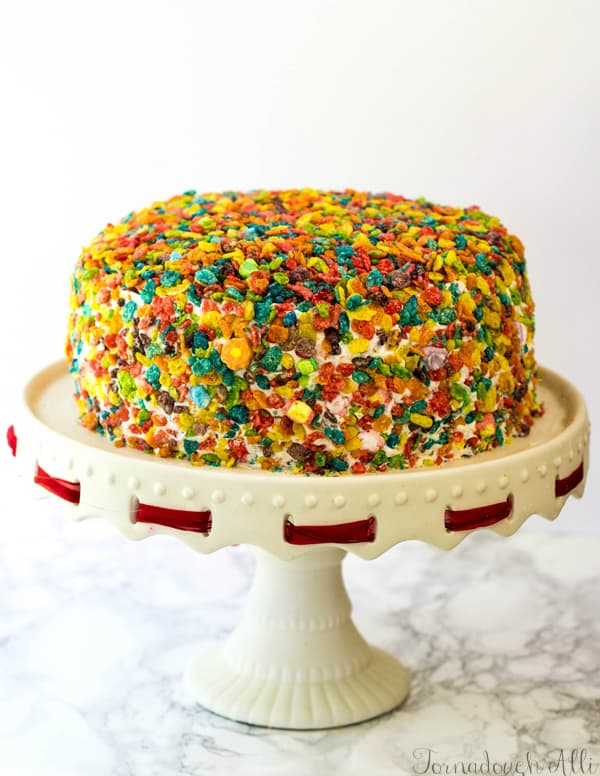 Whole cake on cake stand with red ribbon