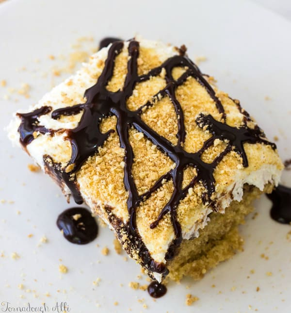 Overhead of S'mores Poke Cake drizzled in chocolate