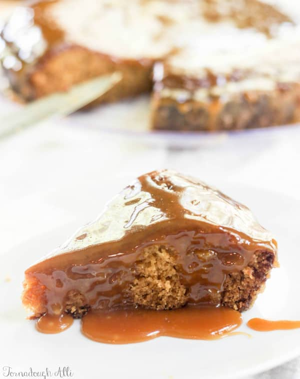 Brown Sugar Toffee Poke Cake on white plate with gooey topping dripping