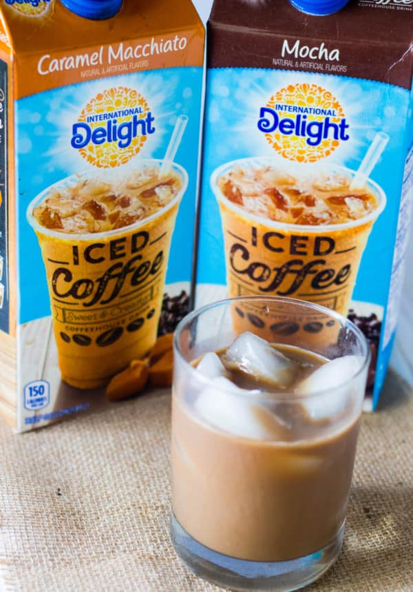 Glaze of iced coffee in front of containers of International Delight Caramel Macchiato and Moca